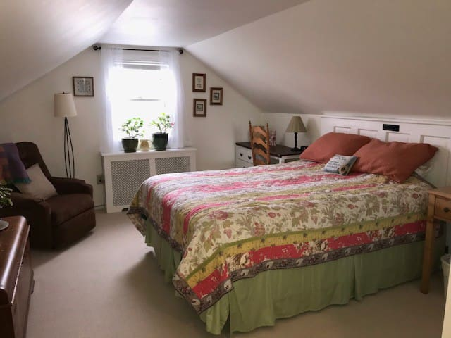 Spacious bedroom with a queen size bed, dresser, closet, desk and comfy chair for reading.