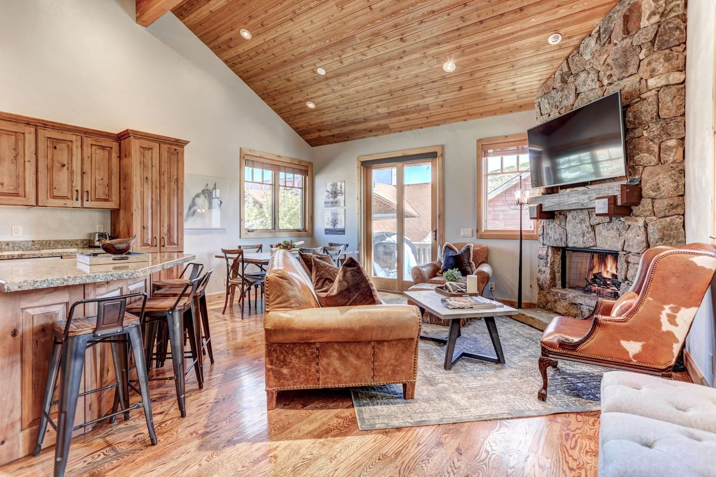 """Living room with fireplace, 55"""" HD Smart TV, dining area and private deck"""