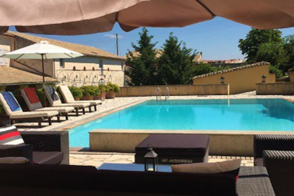 80sq swimming pool with lounge sofas, sun beds, umbrellas and fool view to the old winery and the old Mansion of Vasilakis..