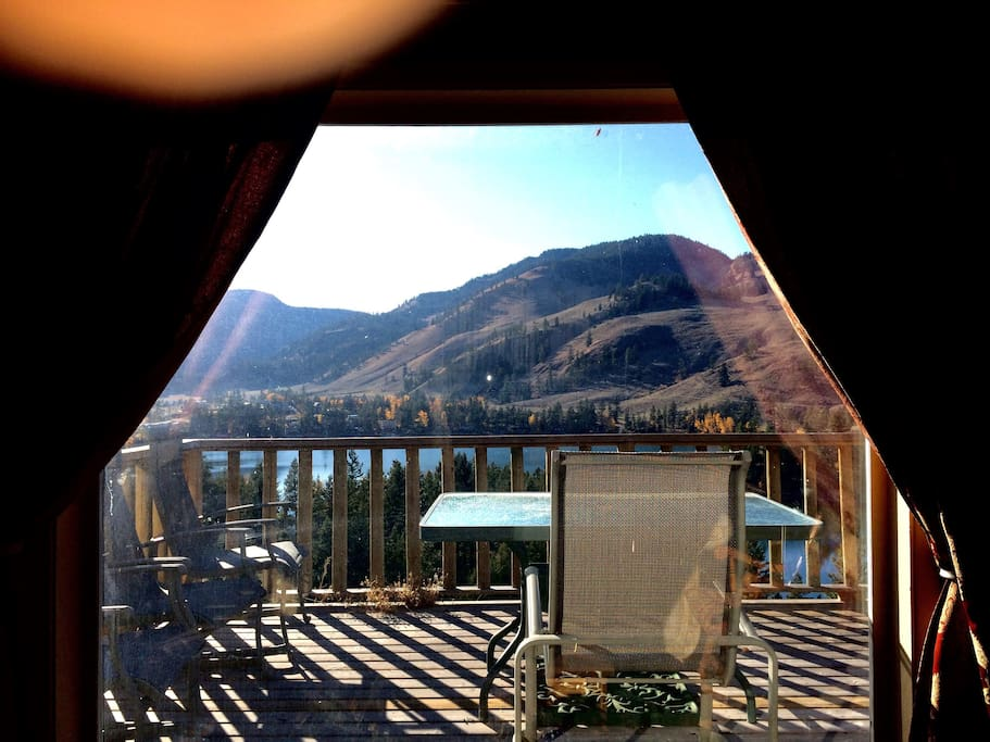 View through cottage living room window onto deck and beyond