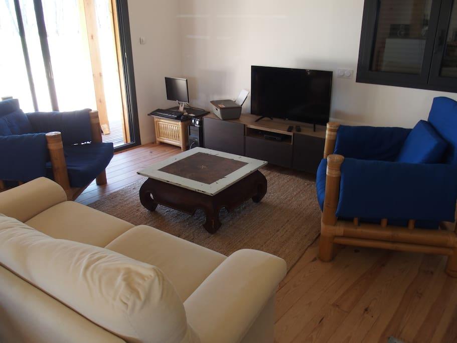 Salon simple avec télévision et coin internet.. vue sur la terrasse..