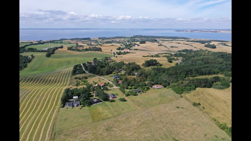 Drone view westwards with Århus in middle of the horizon. The house is red roofed with white balcony (in front).