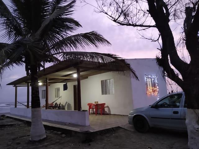 Casa pé na areia com o sol nascente e por do Sol.