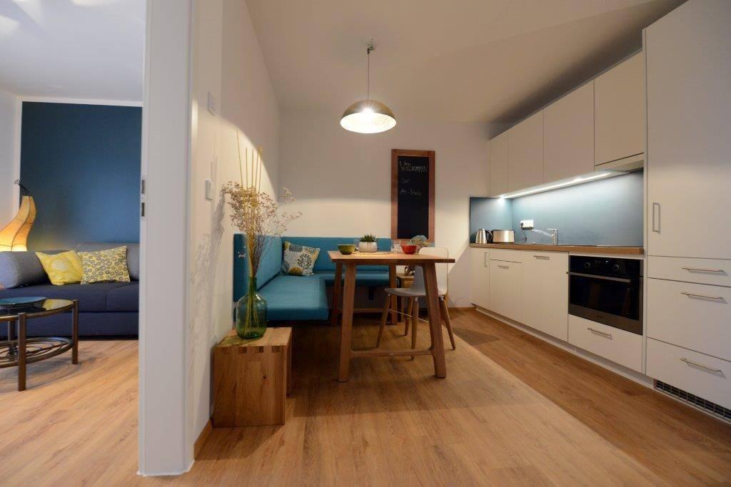 Voll ausgestattete Küche mit Mikrowelle, Backofen, Spülmaschine und Sitzecke