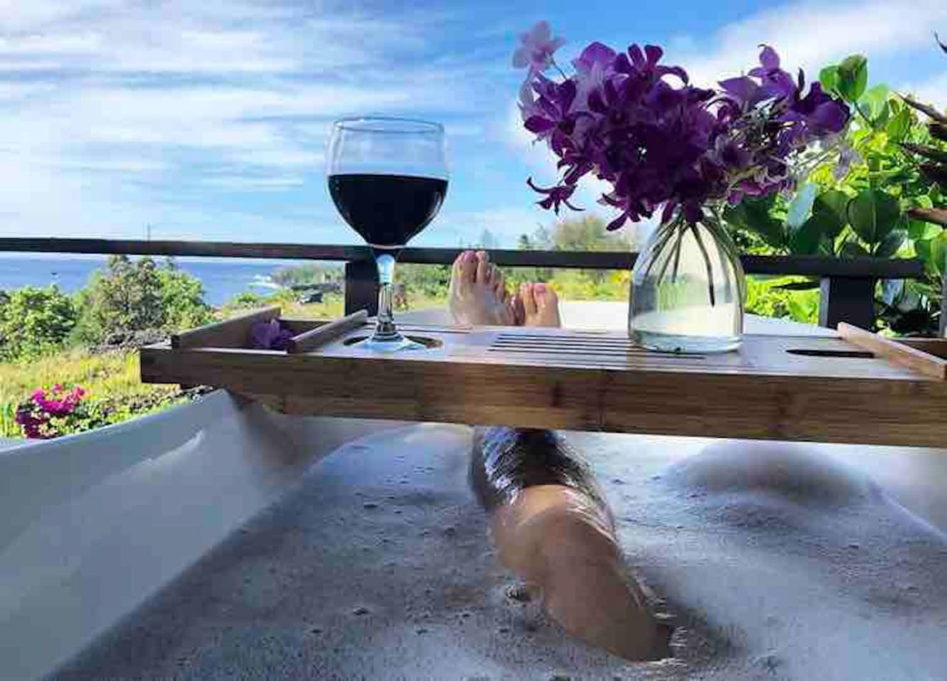 Outdoor tub in the middle of a lush garden  with crazy ocean views...