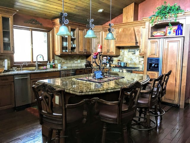 full service Chef's Kitchen with gas stove, trash compactor, granite countertops, open floor plan to dining room and great room and more