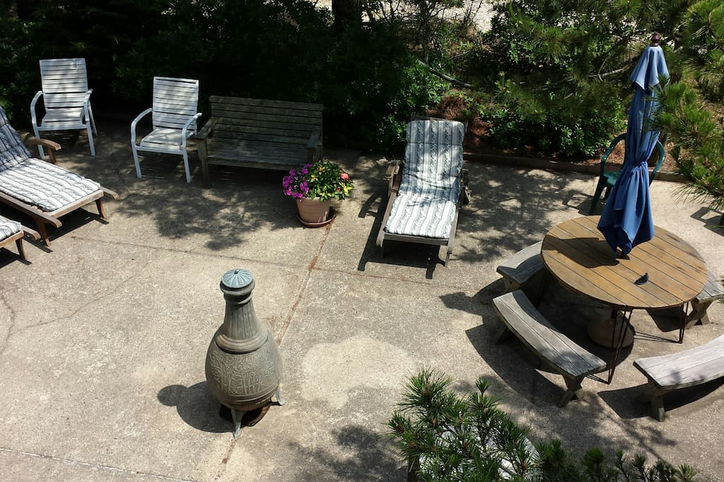 Large, outdoor, private patio with two grills, outdoor dining, and handmade chaise lounges for relaxing.