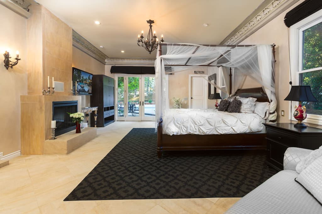 "The 1200 square foot master suite features French doors that open to the pool/patio area, a cal-king canopy bed, a romantic LED lit fireplace, 50"" flat screen tv, and ample wardrobe space in addition to a walk-in closet."