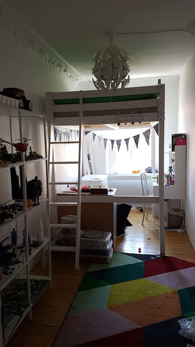 Bedroom with elevated bed. The bed is 140 cm wide and can fit 2 children. Close to the ceiling, about 70 cm free space between bed and ceiling.