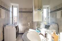 Bagno finestrato e soleggiato con lavatrice e doccia.