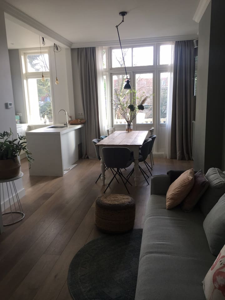 With its high ceilings and doors opening to a sunny balcony, the living room has a fully equipped open kitchen, a dining area and seating area with tv.