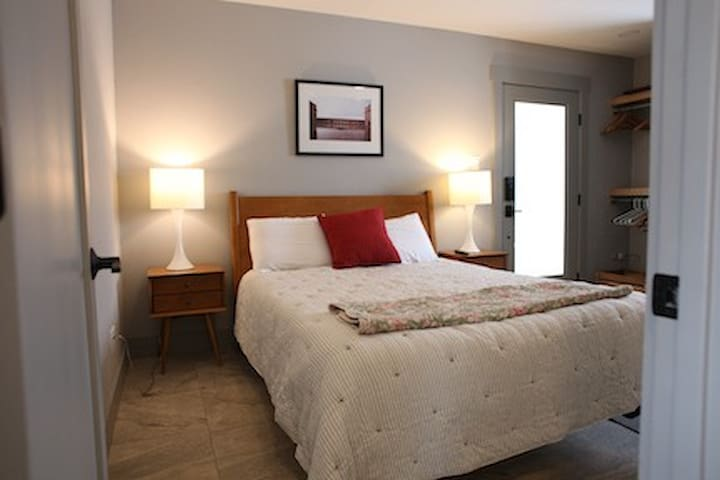 Bedroom.  Queen bed.  Door leads to back deck and off-street parking.