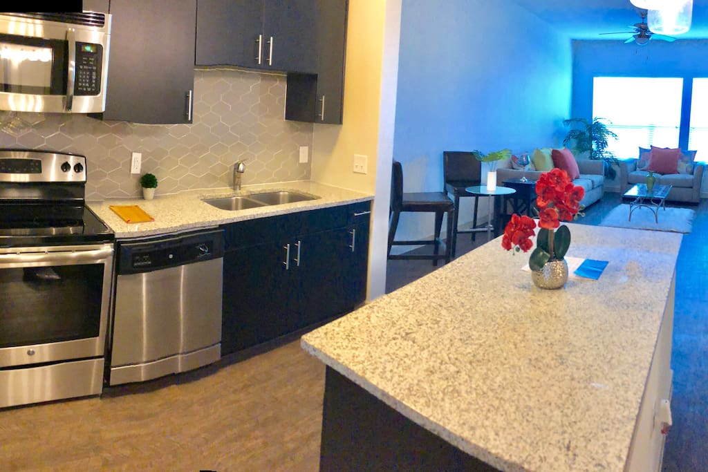 Kitchen island with granite counter tops, built-in microwave , electrical stove top , oven , sink with disposal, stainless still fridge, dishwasher