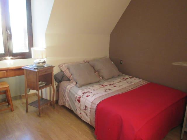 Chambre lumineuse avec lit double et table de nuit