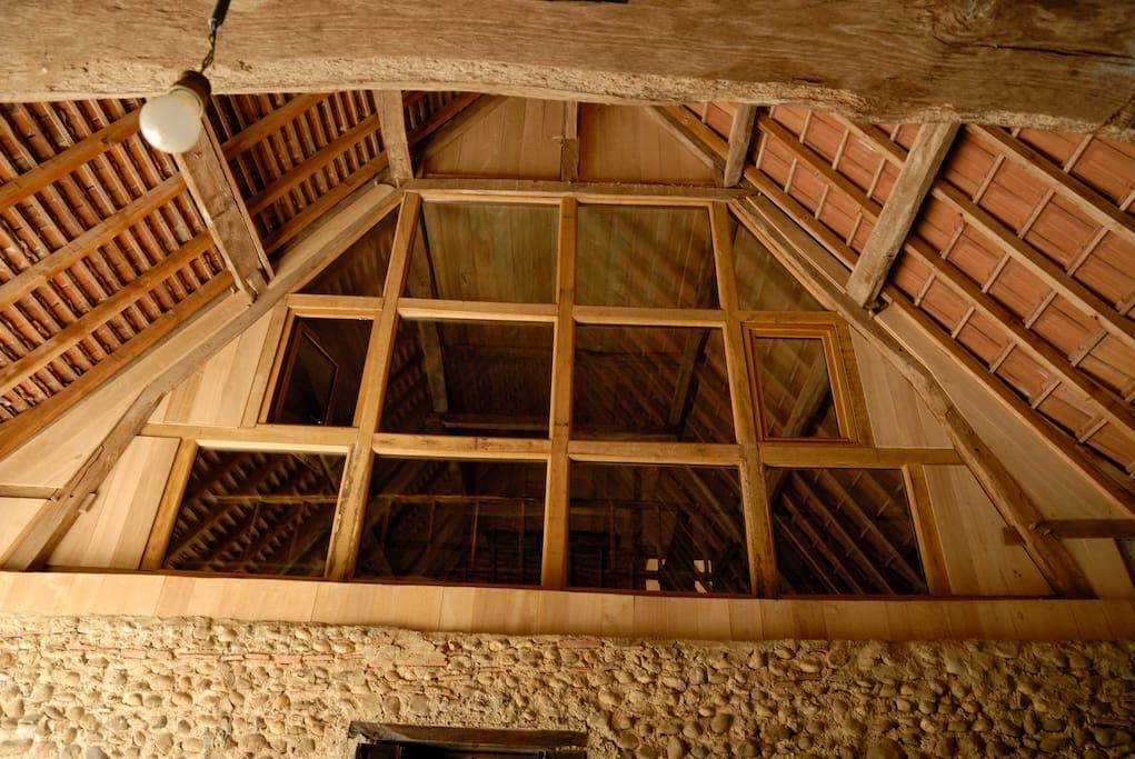 """Chambre """"Sack"""" avec son mur en vitres pour admirer la charpente et capter la lumière."""