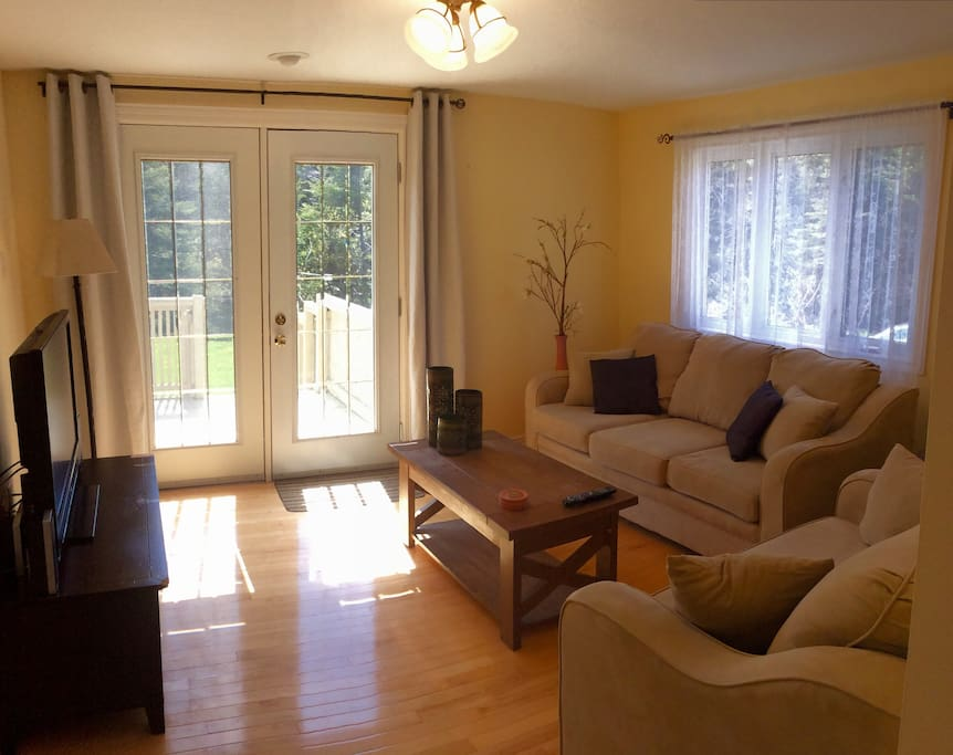 Bright, cozy living room with flat screen, cable TV. Walk out to your private deck and enjoy your morning coffee.