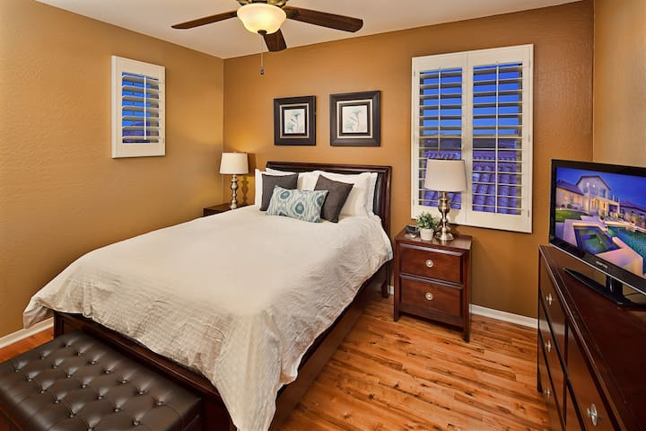 Spacious bedroom with ample closet space, fan, and TV.