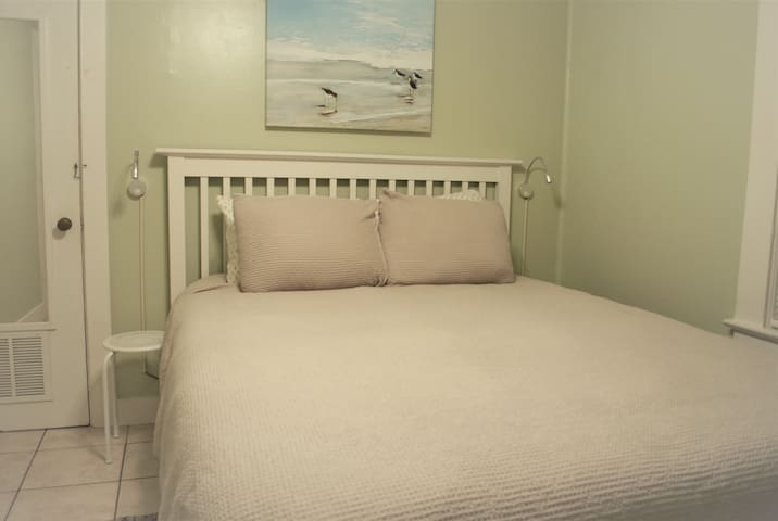 Comfortable queen bed with reading lights in middle bedroom