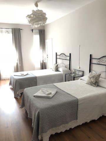 Habitación doble con dos camas y baños compartidos