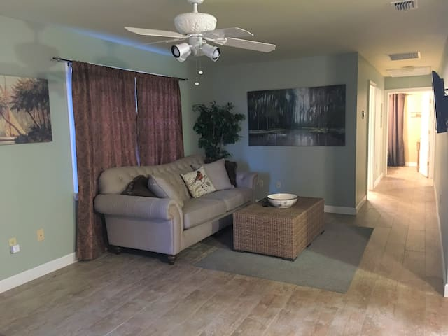 New couch 2018. TV hung on wall to the right. No local channels. Hallway to bedrooms
