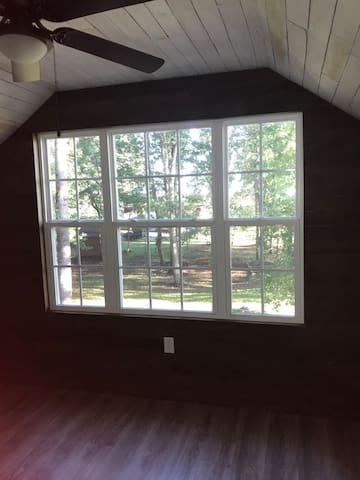 Large window in master bedroom over looking beautiful scenery.