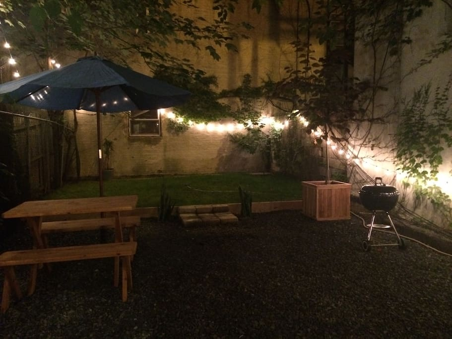 Backyard at night with BBQ, fire pit, picnic table, umbrella and lights (Fair warning: Plants died over the winter)