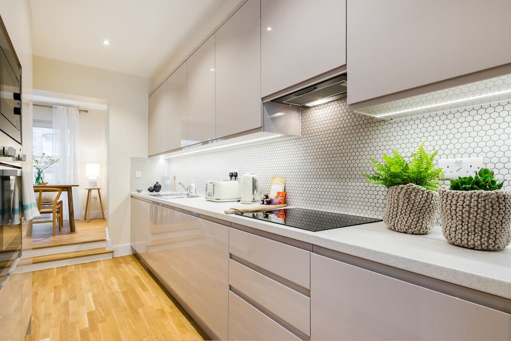 The sleek and modern kitchen is brand new.