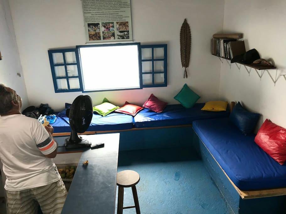 Espaço comum com três sofás de alvenaria sendo que o da direita transforma em uma cama de casal.