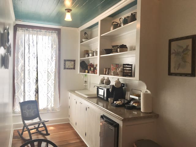 "Directly outside of ""John Doe's room"" is a small non-cooking kitchen. It has a microwave, mini-refrigerator, coffee maker with coffee supplies. There is a table with four chairs to relax and enjoy your coffee. This window faces S. Crockett St."