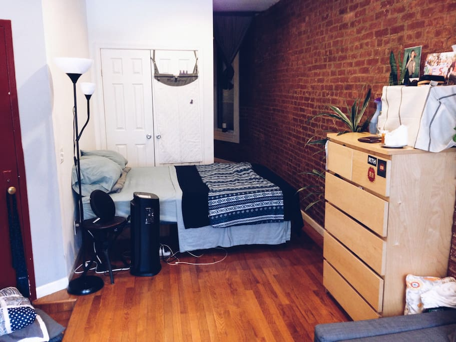 Queen sized bed and entrance to one side of the apartment (red door)