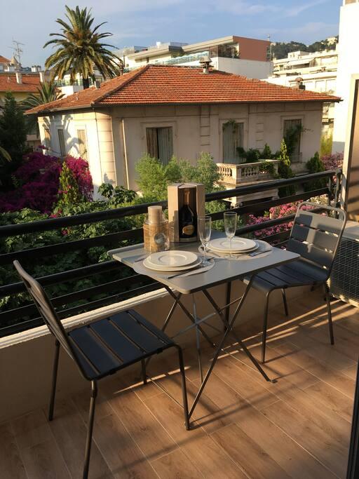 Grand balcon avec table et chaises  et vue magnifique sur le jardin