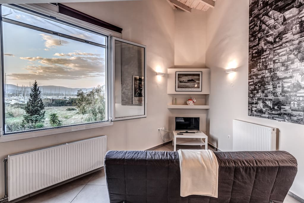 Big window leaves plenty of light into the room with view to an open space and Gouvia marina.
