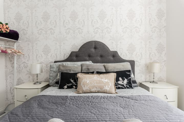 The first bedroom has a beautiful upholstered bedstead