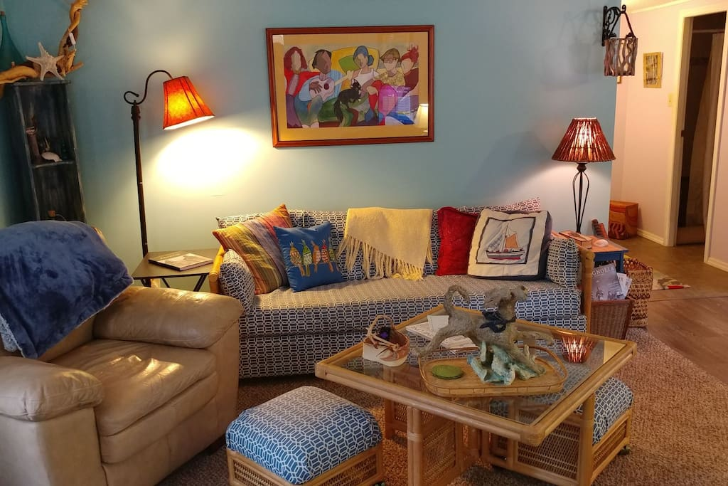 There is ample seating in the  relaxed Beach Inspired living room It is the  perfect place for playing one of the many  provided games. doing a puzzle, streaming movies and  favorite shows or reading a good book by the fireplace.