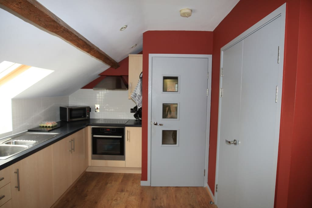 Kitchen area with oven hob, microwave and exposed beams off living area