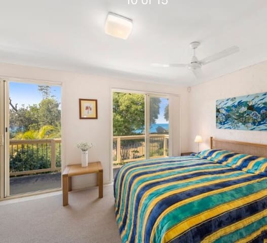 Master Bedroom  and private balcony with view to bush-land and beach 50 meters from back door.