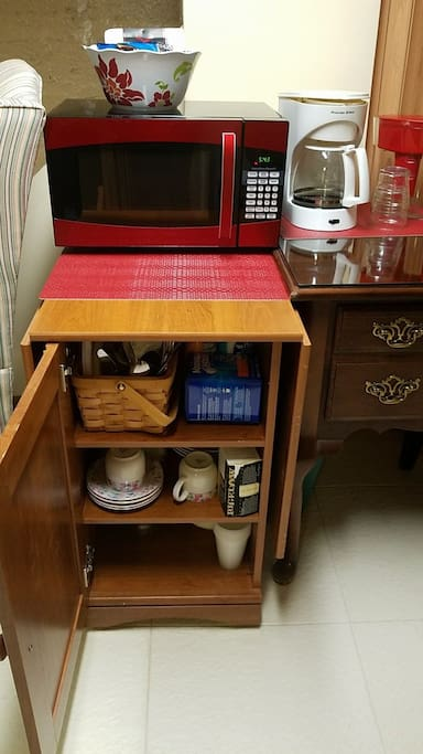 Microwave, coffee pot with coffee and tea, Brita, dishes, silverware and paper prouducts.