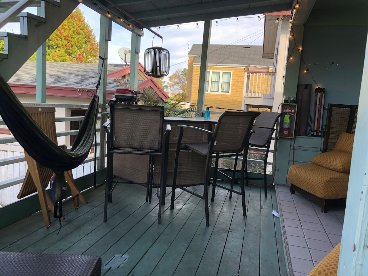 Private Back deck with comfortable chairs, bar area, hammock, cool lighting, and small grill