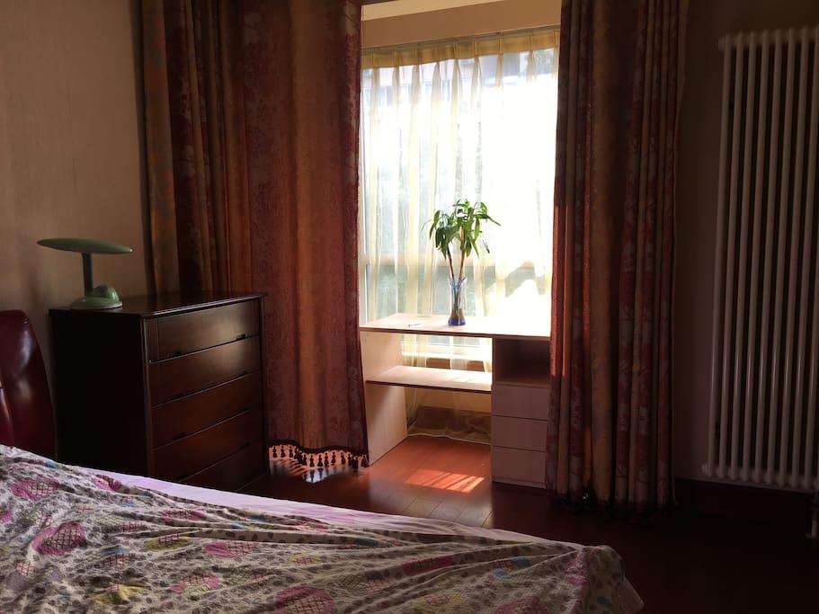 宽敞的大卧室,1.8米的大床,柔软舒适,内藏的阳台,面对屋外的成荫绿树,室内有提供衣柜、五斗橱、写字桌,方便访客的独立使用