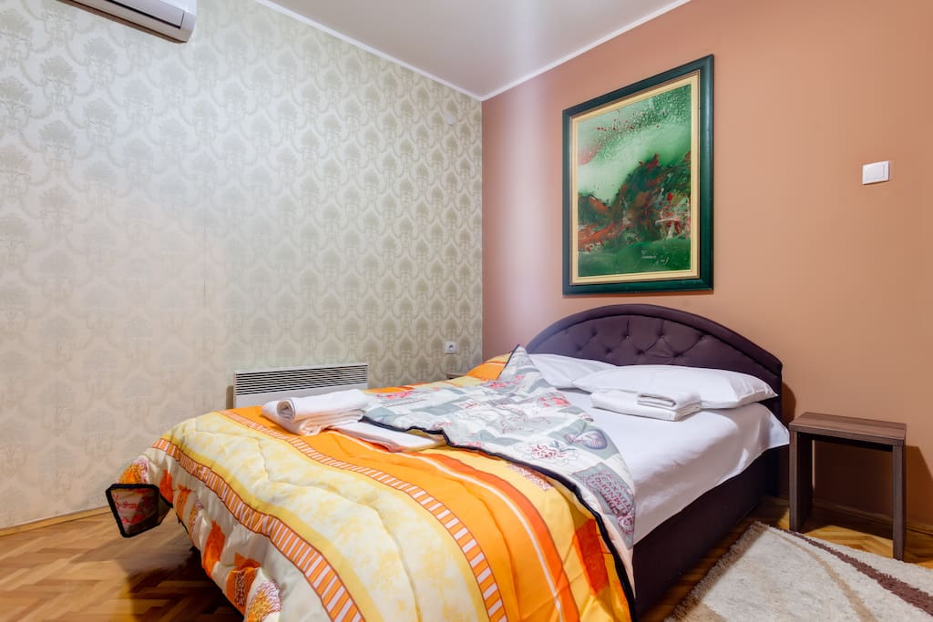 Double bed with night stands is in the bedroom. Wall paint and decorations should be calming, so our guests can fall asleep easily.
