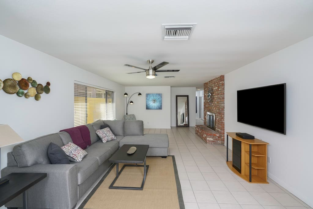 """Living room sits 6 comfortably with a 70"""" smart TV; perfect for entertainment. Remote controlled fan/light. Two single seated lounging area in front of the fireplace with a clear view of the TV."""
