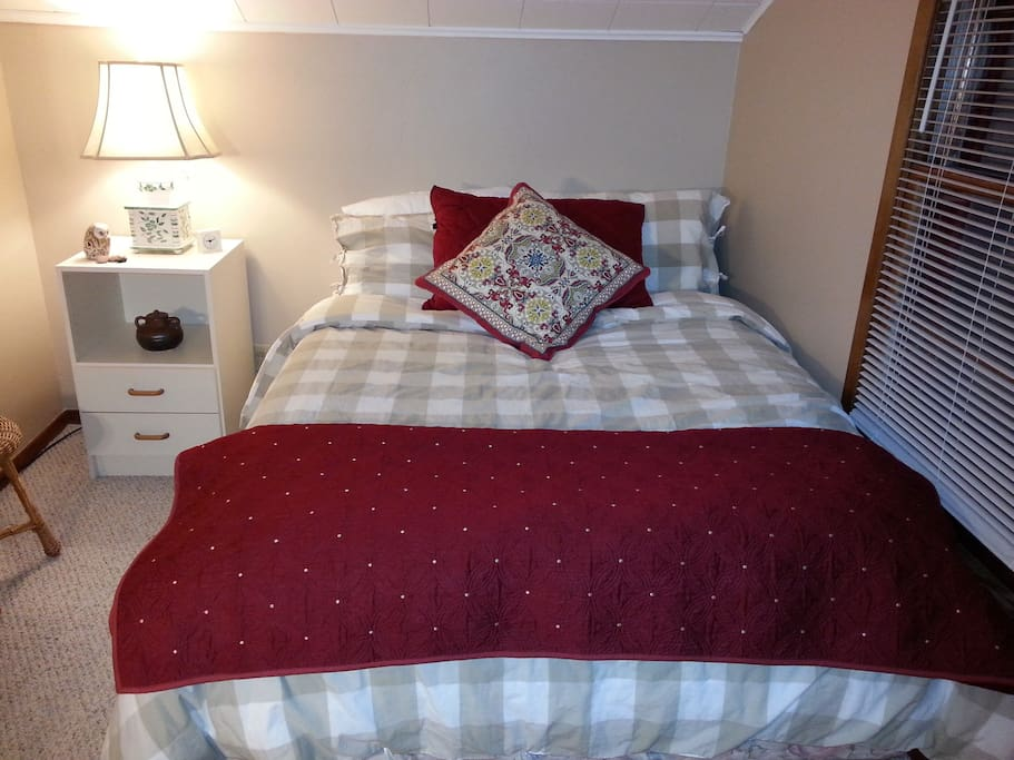 Comfy double bed by two windows with sunny garden, backyard view.
