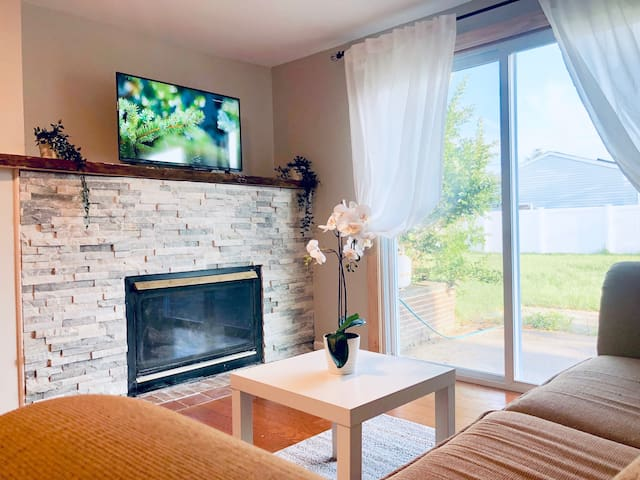 Sunlit Family Room with a gas fireplace, Chromecast, Smart TV, Netflix and sleeper sofa.
