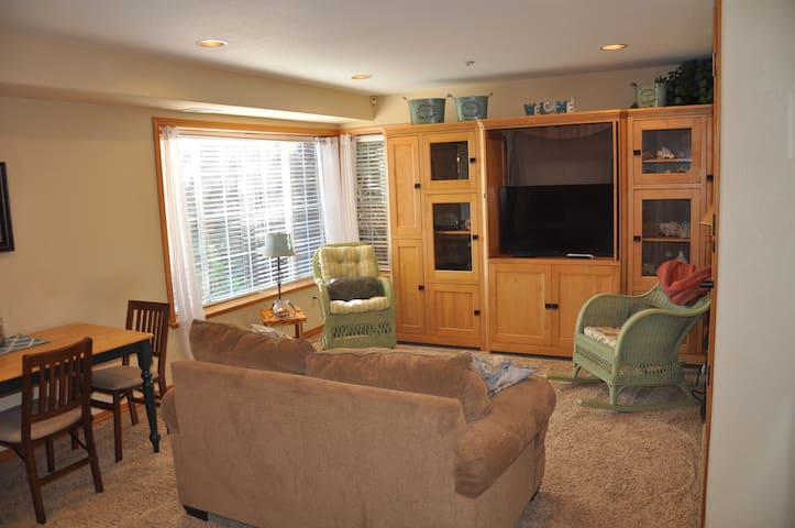 Living area with small sofa, 2 chairs, and table with 4 dining chairs. Smart TV (42 inch) with access to Direct TV.Includes  DVD Player. Good natural light in this room.
