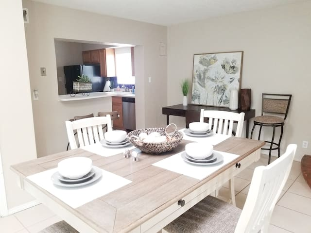 Dining room with large kitchen table, seating for two at the little kitchen nook and a large desk work space.
