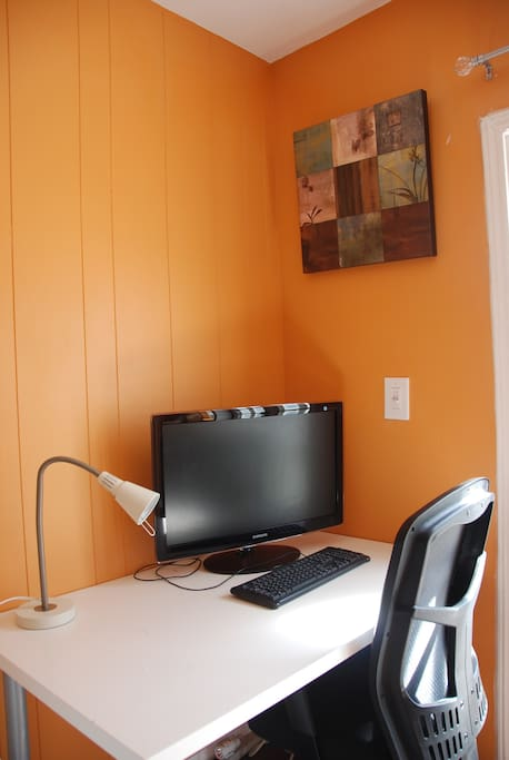 Desk with flat screen monitor, lamp, and external keyboard and mouse makes for a very comfortable work space from home.