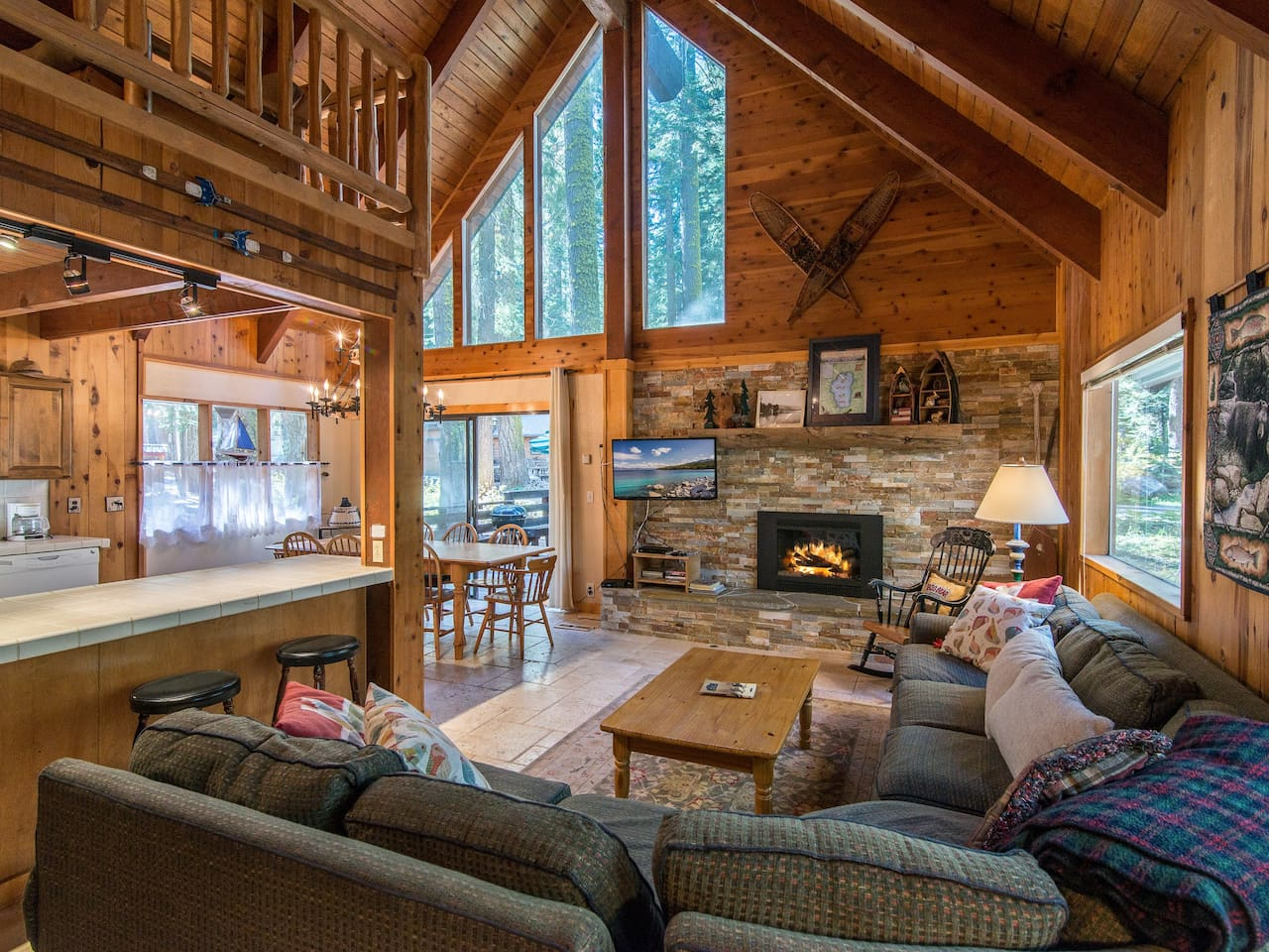 """Welcome to Homewood! The main living area boasts high vaulted ceilings, charming knotty pine finishes, and a 42"""" flat screen TV."""