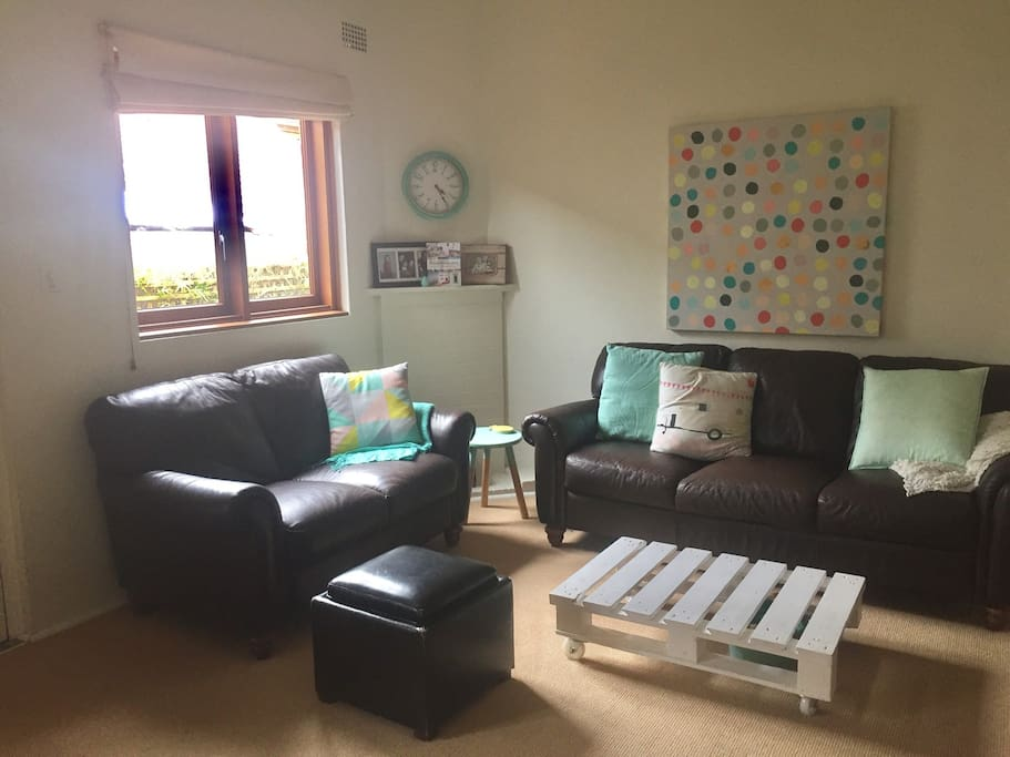 Large lounge room next to kitchen, includes one 3 seat sofa, 1 two seat sofa and 2 chairs. TV with cable and an apple box. Bookshelf of books and drawers filled with games for all ages.