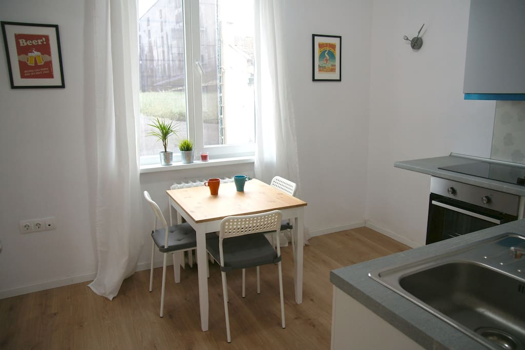 Kitchen with a small dining table, fridge, oven, hotplate, coffee machine, toaster