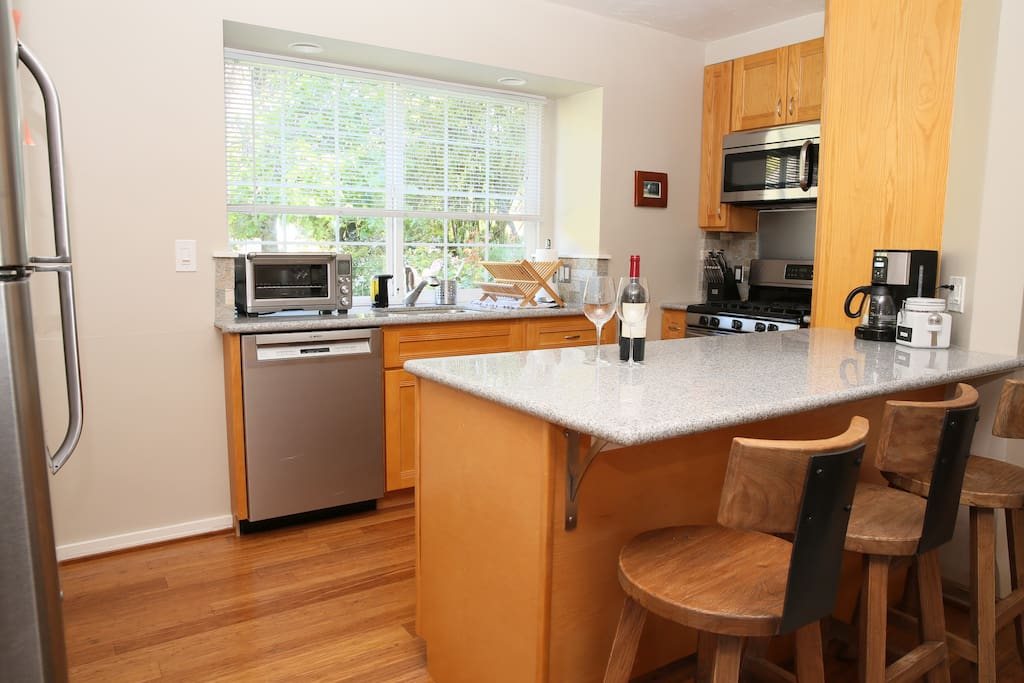 Well lit kitchen and granite counter island make a bright and friendly cooking and casual seating area.